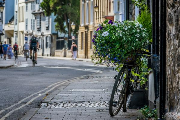 An image of Oxford's street, with an image of a bike against the wall